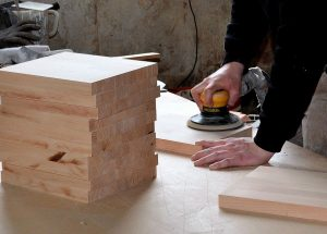 Trim Carpenter sanding wood for use on a job.