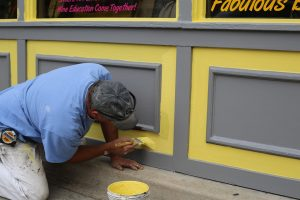 Painter finishing a job before turning over a new house to its owner.